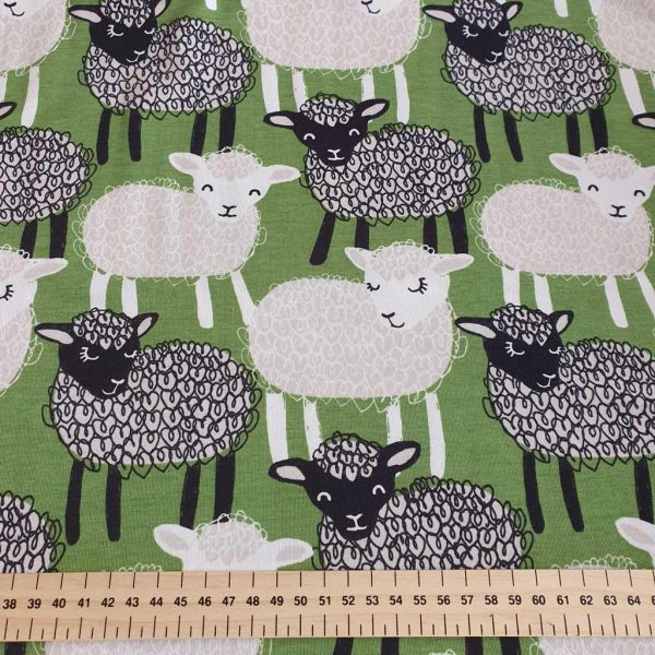 Black and white sheep on green organic jersey fabric