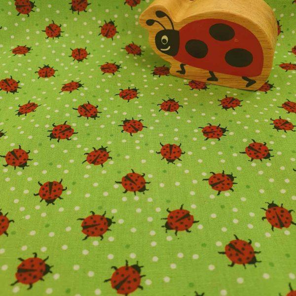 Red ladybirds on green cotton poplin fabric