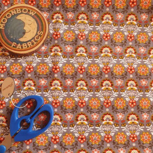 Orange flowers on grey corduroy fabric