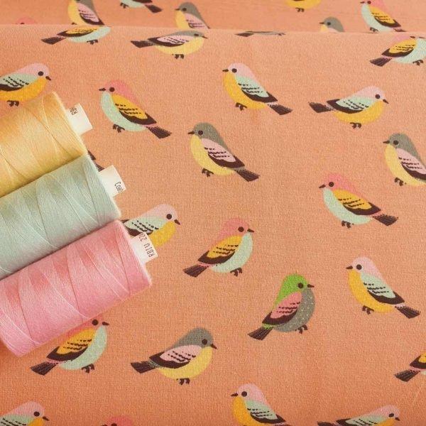 Birds on salmon coloured jersey fabric