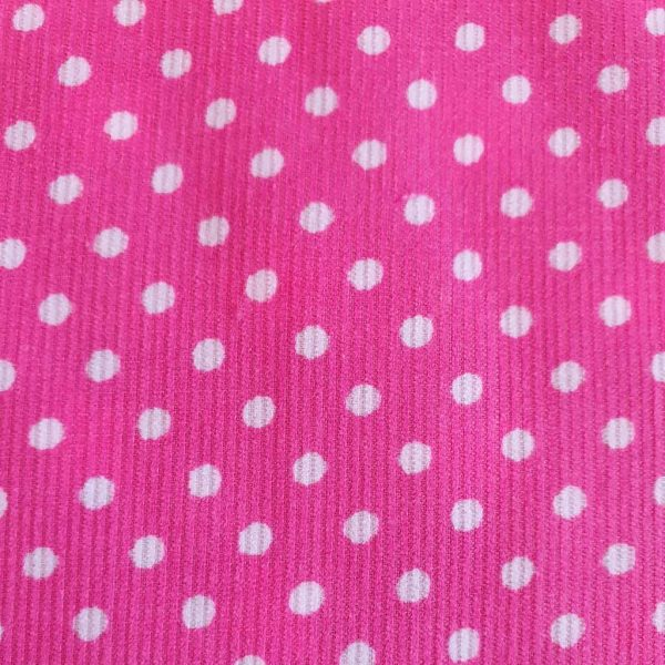 Close up of bright pink corduroy fabric with white polkadot print