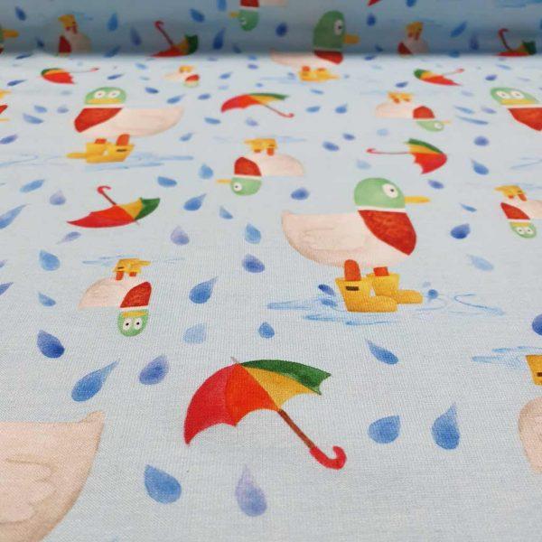 Puddles, ducks and umbrellas on blue organic jersey fabric