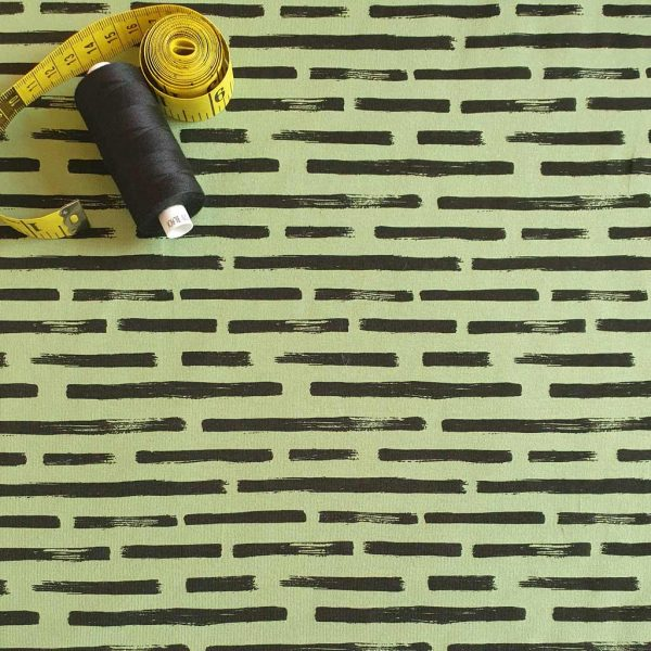 Black dashes on light green background jersey fabric